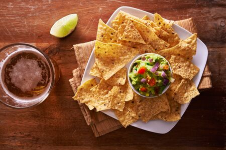 top down: tortilla chips with guacamole and beer shot top down Stock Photo