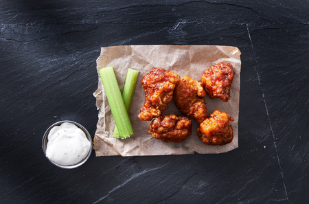 bbq chicken hot wings on parchment paper with ranch and celery Stock Photo
