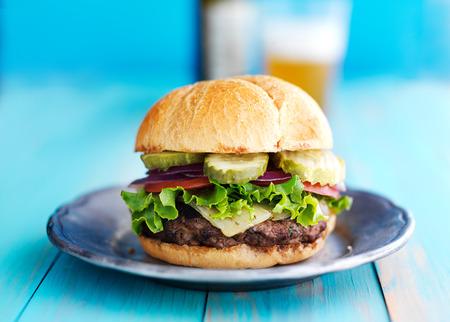 cheeseburger met bier op de achtergrond op rustieke versleten geschilderde planken Stockfoto