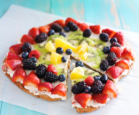 colorful fruit pizza with berries and cream cheese on cookie crust