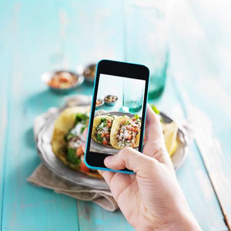 plato de comida: toma la foto de tacos con el tel�fono inteligente Foto de archivo