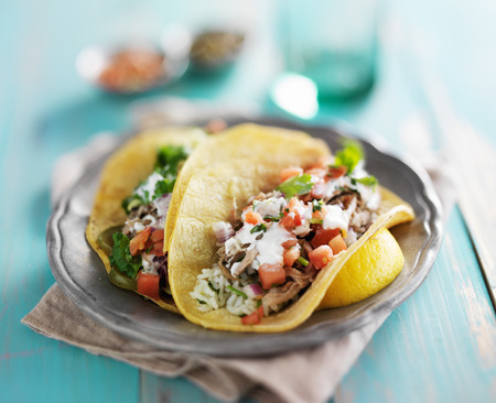 mexican authentic carnitas tacos with sour cream and corn tortilla