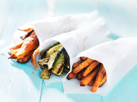 trio: trio of carrot, zucchini, and sweet potato fries wrapped up in wax paper cones Stock Photo