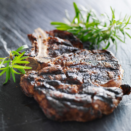 grilled prime rib beef steak with rosemary on slate Stock Photo