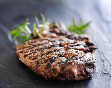 grilled prime rib beef steak with rosemary on slate photo