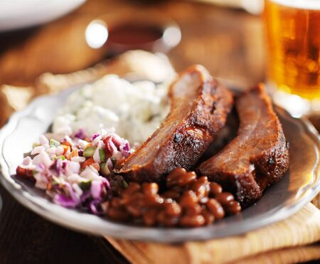baked beans: barbecued spare rib meal with beer and fixings like baked beans, cole slaw, and potato salad Stock Photo