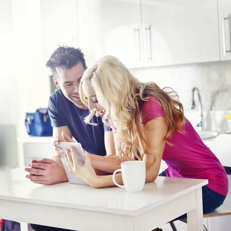 happy couple shopping online or watching videos on tablet in kitchen photo