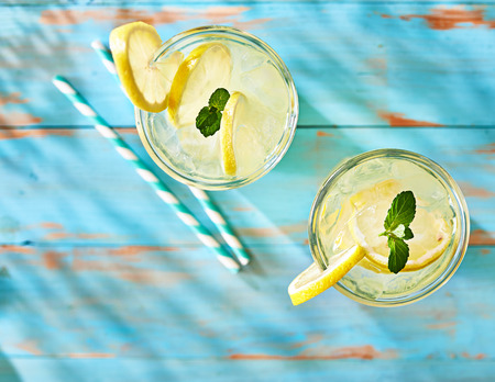 two glasses of lemonade shot from overhead view on rustic table top Imagens