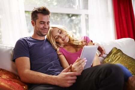 couple on couch: couple watching videos or shopping on tablet cuddling on couch at home