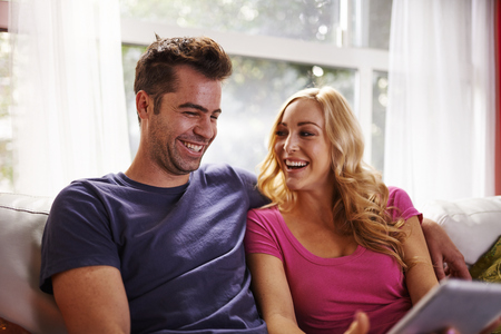 couple on couch: happy couple using table on couch together Stock Photo