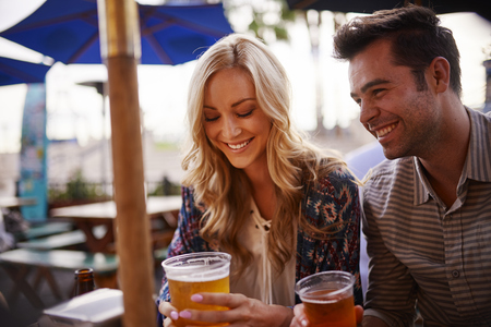outdoors: couple drinking beer at outdoor bar Stock Photo