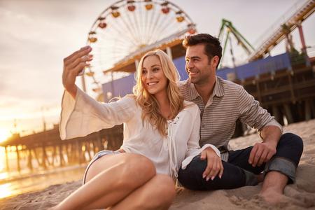 romantico: pareja rom�ntica teniendo selfie en sonica monica que se en la arena Foto de archivo