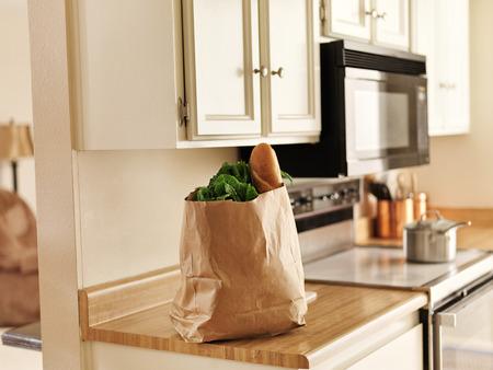 부엌 카운터에 앉아 매장에서 갓 구입 한 식품의 종이 식료품 가방
