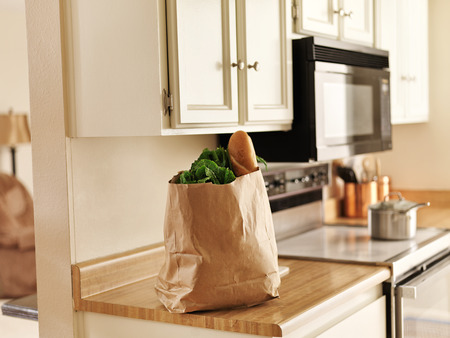 full: paper grocery bag of freshly bought food from store sitting on kitchen counter Stock Photo