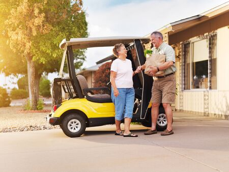coming home: active senior couple coming home with groceries on golf cart