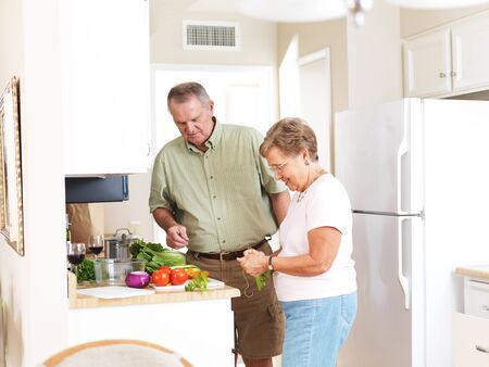 elderly husband and wife making dinner together in kitchen photo