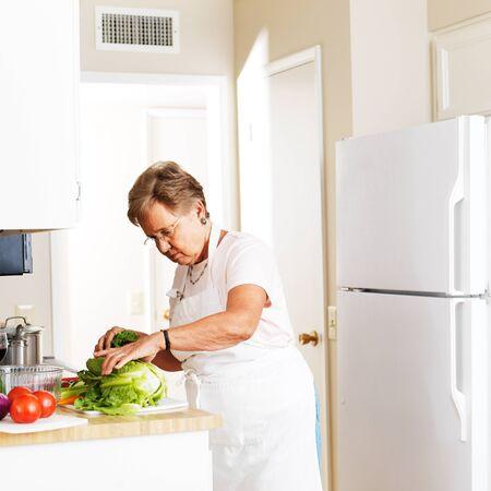 cutting vegetables: elderly woman in kitchen cutting vegetables