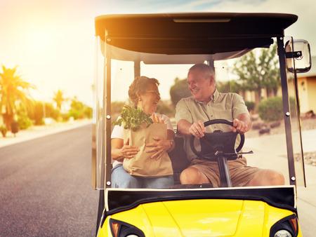 active elderly senior couple getting groceries on golf cart Standard-Bild
