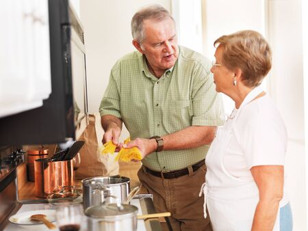 senior couple cooking pasta in kitchen at home photo