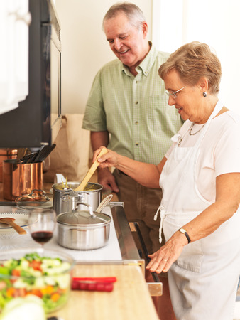 elderly couple cooking together in kitchen
