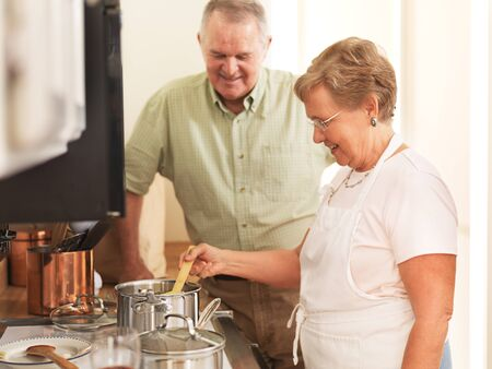senior couple together in kitchen cooking pasta photo
