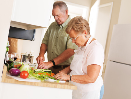 elderly senior couple at home preparing vegetables for a meal photo