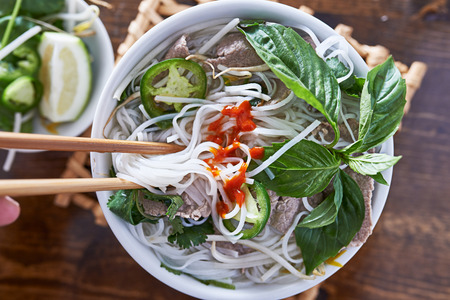 top down: eating beef pho with spicy sriracha sauce shot top down Stock Photo