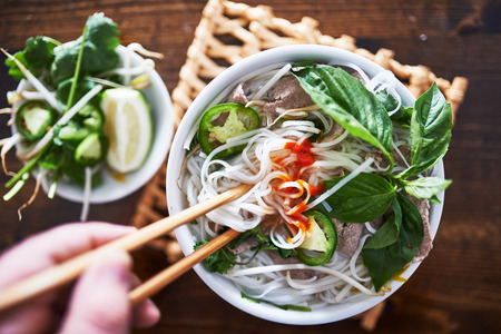 comiendo: pho vietnamita con salsa picante sriracha tiro de arriba hacia abajo