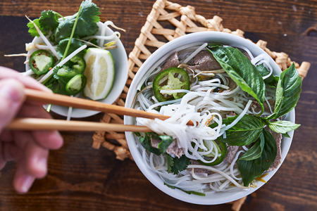 eating a bowl of pho with chopsticks Imagens