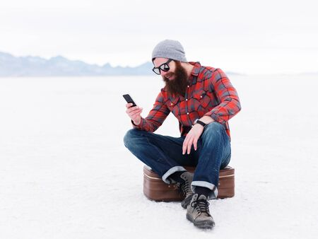 suitcase: lost hipster with beard with suitcase using smartphone on salt flats