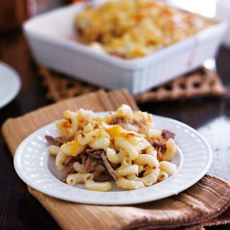 shredded cheese: plate of baked macaroni and cheese casserole with barbecue pulled pork