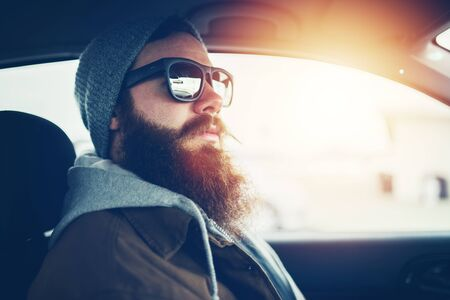 beanie: bearded hipster wearing sunglasses inside car Stock Photo