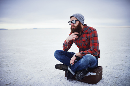 manly: beard lumbersexual hipster sitting on suitcase in deep thought