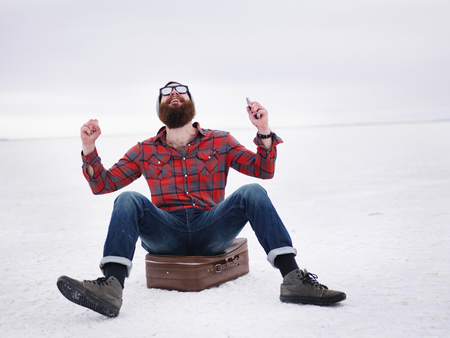 finds: lost hipster on the salt flats sitting on suit case finds what he is looking for Stock Photo
