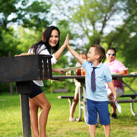 mom son: grilling mom giving high five to son at picnic Stock Photo