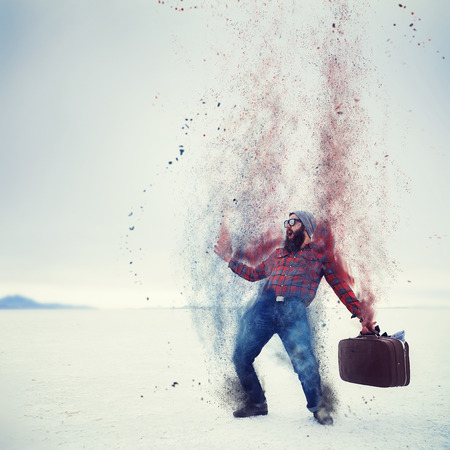 turn away: hipster with beard and suitcase turning into dust on the salt flats