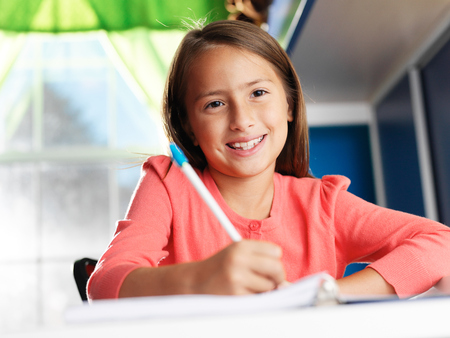 work from home: little girl doing home work smiling