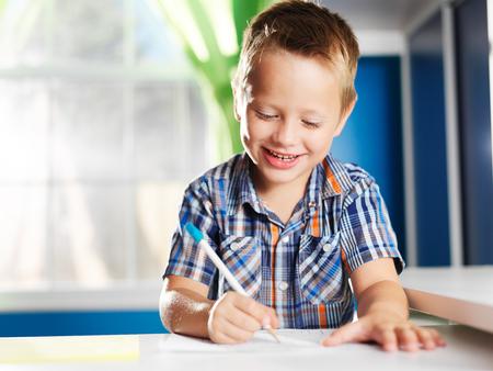 gelukkige kleine jongen in zijn kamer huiswerk doet