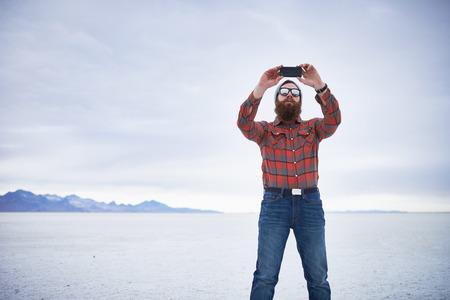flannel: lone lumbersexual hipster taking selfie in salt flats Stock Photo