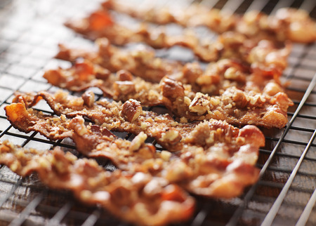 candied bacon with pecans and brown sugar cooling on baking rack 스톡 콘텐츠