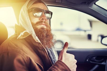 viso di uomo: pantaloni a vita bassa con la barba seduto in auto dando il pollice in alto Archivio Fotografico