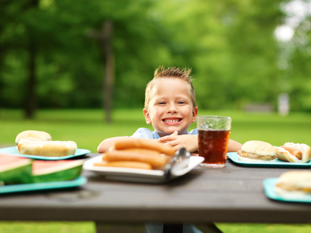 picnic table: happy little boy at picnic table loaded with food
