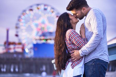 parejas jovenes: romántica pareja besándose delante del muelle de Santa Mónica Foto de archivo