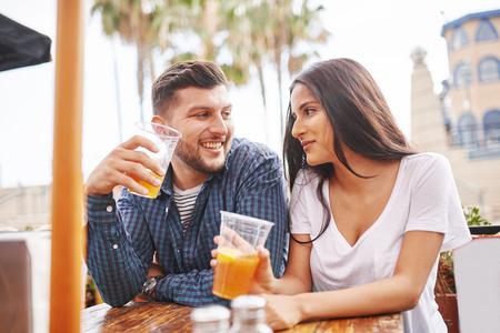 persona alegre: pareja hispana divirtiéndose y bebiendo cerveza durante la conversación