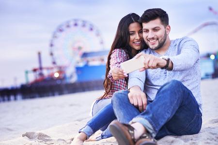 romantic couple sitting in sand taking selfie with santa monica pier in background Standard-Bild