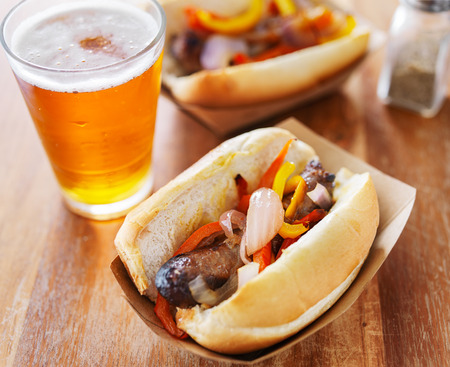 grilled bratwurst covered in onions and peppers with beer