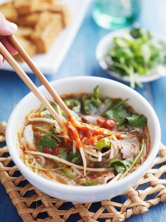 santa cena: comer un plato de sopa de carne Pho Tai vietnamita con sace sriracha picante Foto de archivo