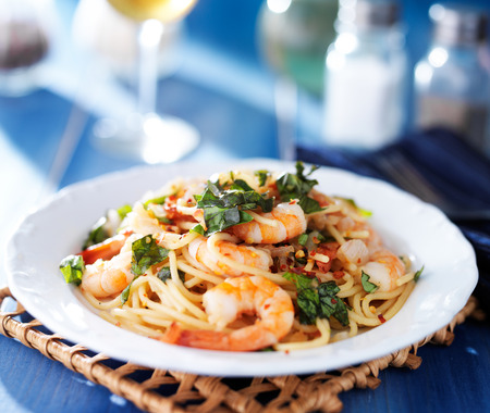 spaghetti dinner: shrimp spaghetti pasta with fresh basil and crushed red pepper Stock Photo