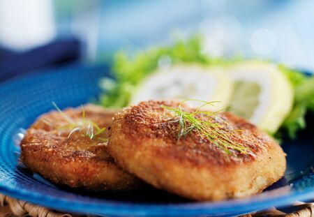 maryland crab cakes with lemon and lettuce on blue plate with dill garnish