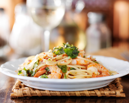 eye level view of shrimp spaghetti pasta on a white plate and white wine in background Stock Photo